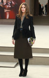Olivia Palermo worked ladylike with a twist in a knee-length olive skirt, a printed blouse, black shearling blazer, and a funky printed clutch at Burberry Prorsum.