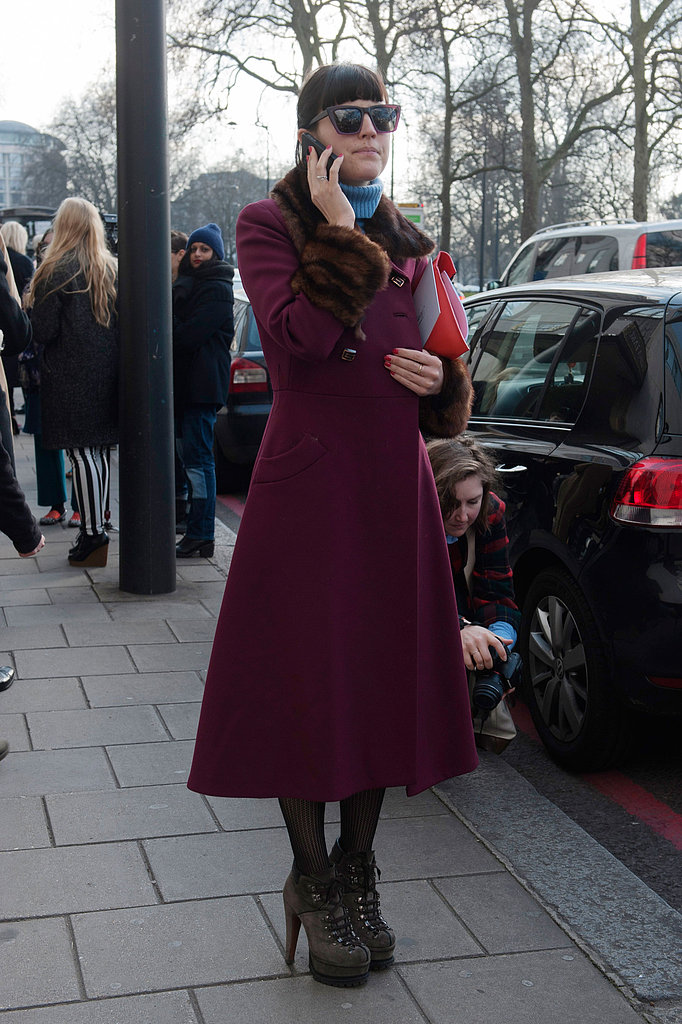 This showgoer's utilitarian ankle boots juxtaposed a berry-hued ladylike coat.