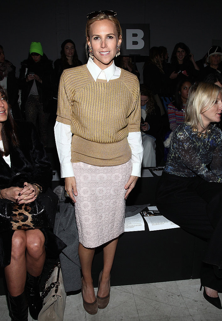 Tory Burch attended he Kimberly Ovitz Fall 2013 show in NYC looking professional with a feminine twist in a white blouse, short-sleeved sweater, and printed pencil skirt.