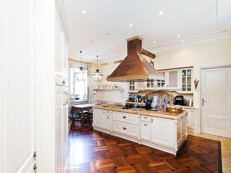 The kitchen's traditional design is enhanced with copper accents, classic hardwood floors, and lantern pendant lights. Source: Sotheby's