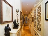 Dark statues and large artwork in beautiful gold frames line the apartment's long hallway. Source: Sotheby's