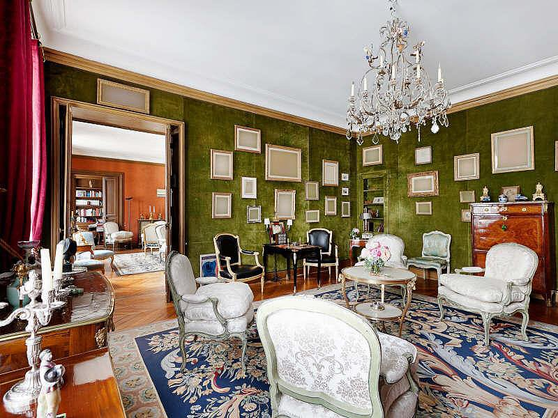 The parlor features a variety of bold, eye-catching details: green textured walls, red curtains, a patterned rug, and several armchair styles. Solid colors, symmetry, and clean lines keep the look from feeling too chaotic. Source: Christie's Real Estate
