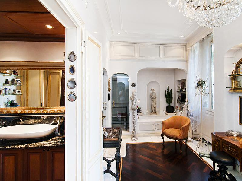 Several of the apartment's more ritzy features appear in the bathroom, too, including a chandelier, statuettes, and a beautiful orange armchair. Source: Sotheby's