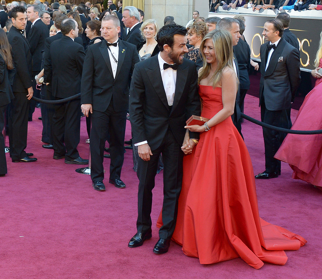 Jennifer Aniston wore a red Armani dress to hit the red carpet with fiancé Justin Theroux at the Oscars in LA.