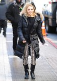 Carrie bundled up in an all-black ensemble — ribbed sweater, puffer coat, and moto boots — and aztec-print pants.