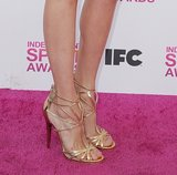 Nina Dobrev's white-and-gold Michael Kors getup got more shine via her strappy gold Jimmy Choo sandals at the Independent Spirit Awards.