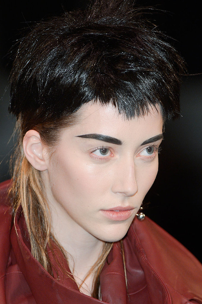 "Guido Palau, lead stylist for Redken, purposefully chose wigs for each of the girls that would clash, more or less subtly, with their natural hair color poking out from underneath for what he deemed a ""boyish, kind of punk quality."""