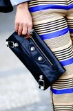 Striped trousers were styled with a black Balenciaga clutch for an edgy touch.