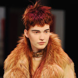 "Guido Palau, lead stylist for Redken, purposefully chose wigs for each of the girls that would clash, more or less subtly, with their natural hair colour poking out from underneath for what he deemed a ""boyish, kind of punk quality."""