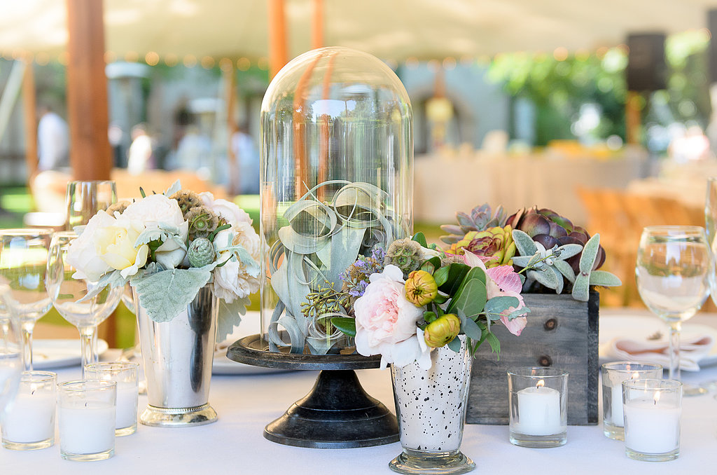Rather than having a grand bouquet that could overpower each table, bell jars and wood boxes created a unique centerpiece.  Source: Juliette Tinnus
