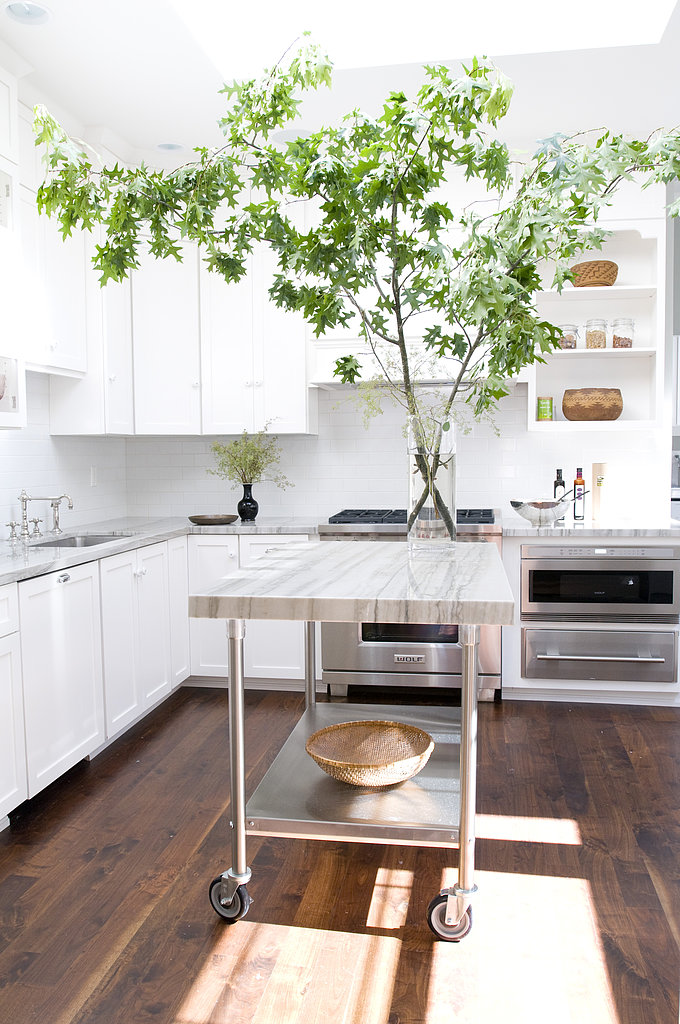 The all-white kitchen is modern yet traditional, while the mobile island is a functional way to provide additional counter space.   Source: Angie Silvy Photography
