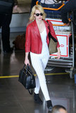 January Jones flew to Paris wearing white print jeans, a bold red leather biker jacket, and a black Givenchy Lucrezia tote ($1,694).