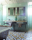 Keeping with the style of the 19th-century antique floor tiles, mint-green tiles on the walls have a relaxing effect without sacrificing color or character.  Source: Elle Decor