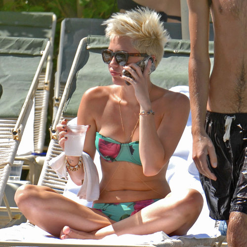 In March, Miley Cyrus lounged poolside in Palm Springs, showing off her svelte figure in a floral bikini, accessorized with gold body jewelry.