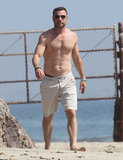Shirtless Liev Schreiber walked on the beach.