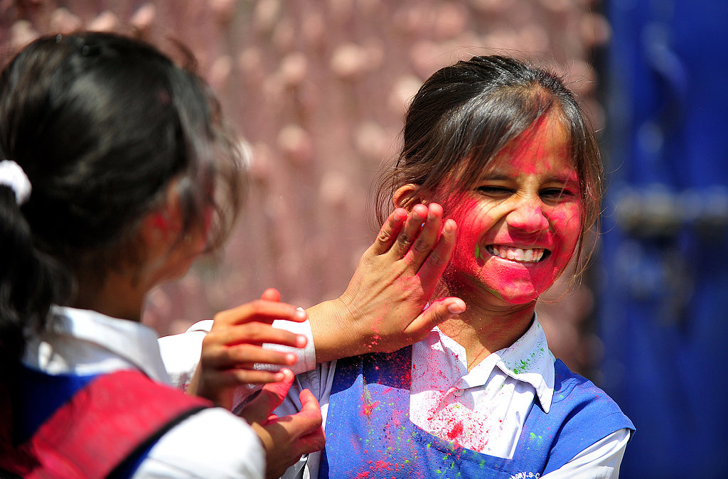 School girls played with colored powder outside a school in Allahabad, India.