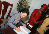 Peng Liyuan signed the visitors' book next to Tanzania's First Lady Salma Kikwete at the Wanawake na Maendeleo Foundation.