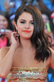 Casual waves, metallic shadow, and neon orange lip colour gave Selena a grown-up visage at the MuchMusic Awards in 2012 . . . and is that a tattoo?