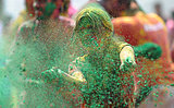 A girl tosses green powder in Hyderabad, India.