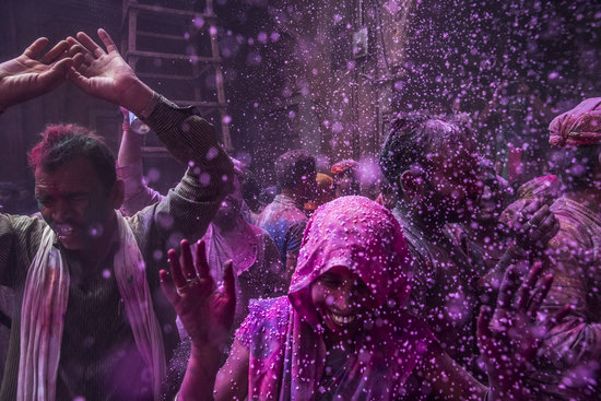 People were coated with colors during Holi at the Banke Bihari temple in Vrindavan, India.