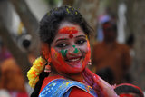 A girl smiled with color painted on her face in Siliguri, India.