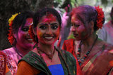 Women beamed with colored powder all over them in Siliguri, India.