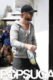 Liam Hemsworth carried his shoes into the gym.