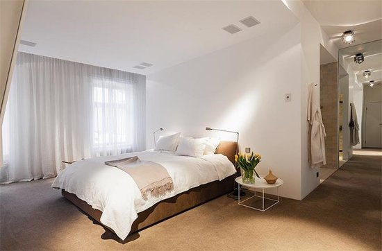 Clean lines, white walls, and neutral bedding make for a serene bedroom. Source: Sotheby's