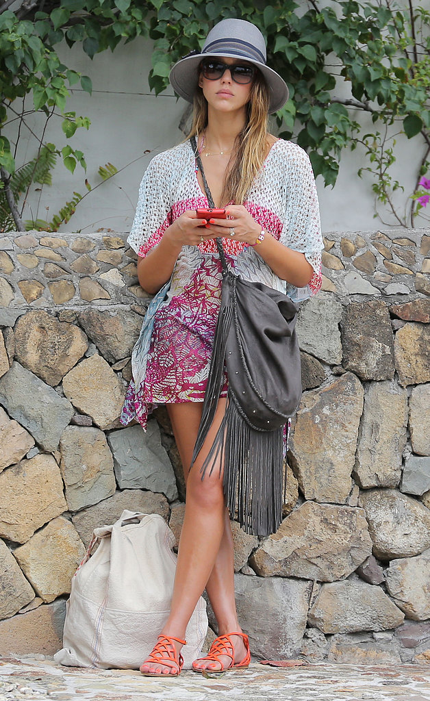 Jessica Alba headed into town wearing a pink printed Missoni caftan, a gray wide-brim hat, gray fringe crossbody bag, and orange strappy sandals ($285) and sunglasses by Tory Burch.