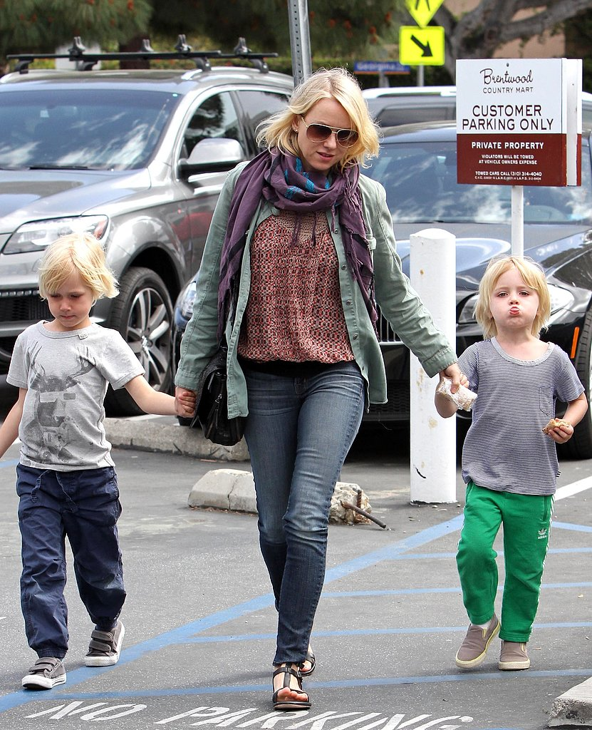 While on mommy duty in LA, Naomi Watts topped her tribal-inspired ensemble with an army green jacket, then tied it all together with a printed scarf.