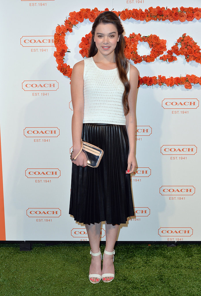 Hailee Steinfeld chose a black-and-white pleated dress to go with her sleek white sandals and Coach Poppy mirrored wristlet.