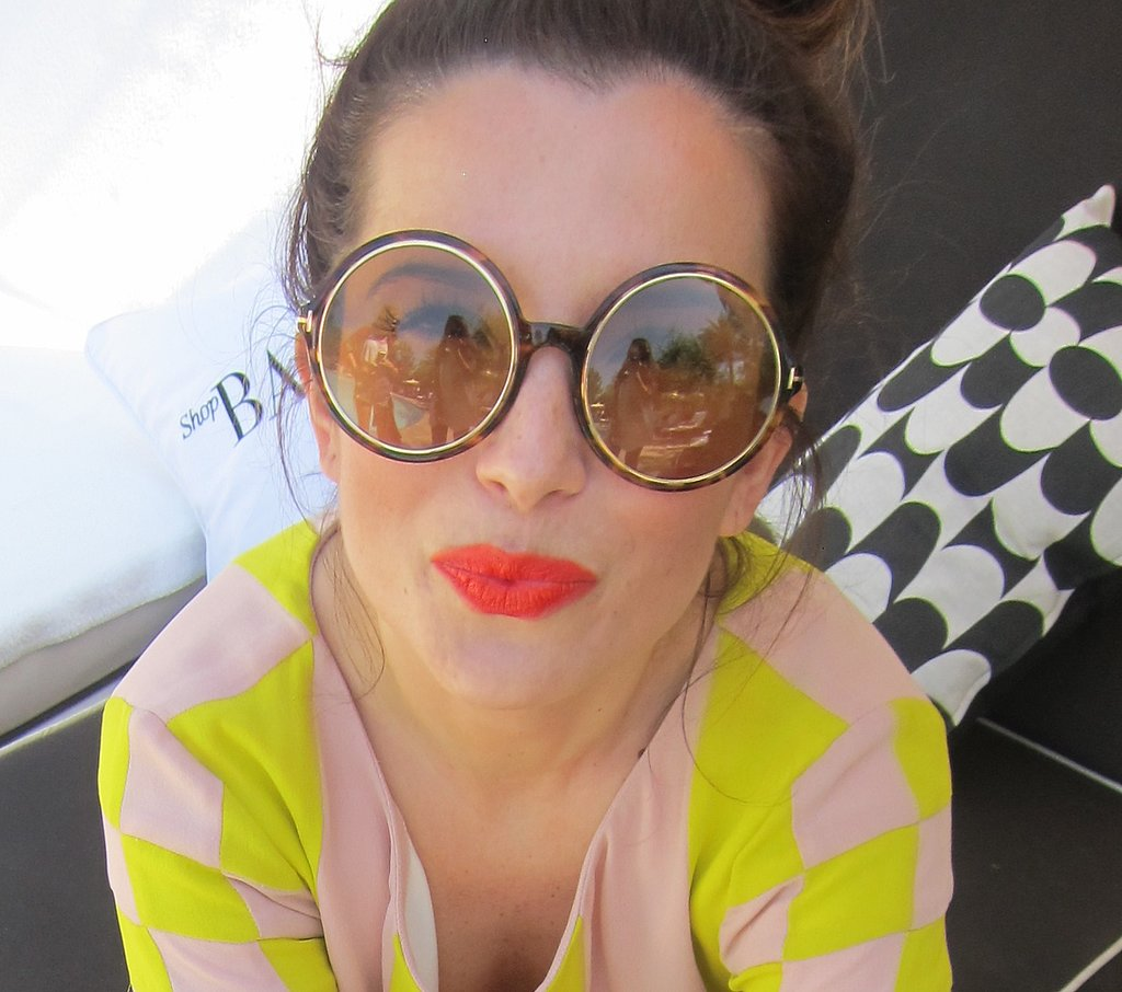 Eccentric and iconic big round glasses are even more powerful when paired with a bright coral lip.