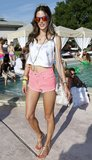 Alessandra Ambrosio looked funky and feminine a pair of pink denim cutoffs, a Lacoste crop top, and mirrored sunglasses at the Lacoste bash.