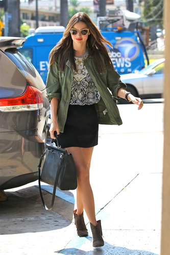 Miranda Kerr showed off a cool-girl outfit complete with a printed tee, an army-green Lily Aldridge for Velvet jacket, a black miniskirt, ankle boots, the 3.1 Phillip Lim Ryder tote, and a pair of glittery gold Miu Miu sunglasses while leaving the hair salon in LA.