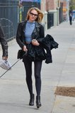 While doing dog-walking duties in NYC, Candice Swanepoel showed off her tough-girl aesthetic in a black leather biker jacket, a blue high-neck crop top, black miniskirt, Rag & Bone booties, and cat-eye sunglasses.
