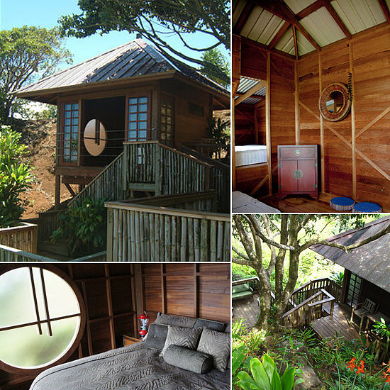 Located in Haiku, this Maui tree house overlooks a private valley. The property features striking double doors, a copper roof, and cool architectural elements including a round bedroom window.