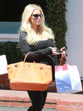 Jessica Simpson carried a large orange handbag.