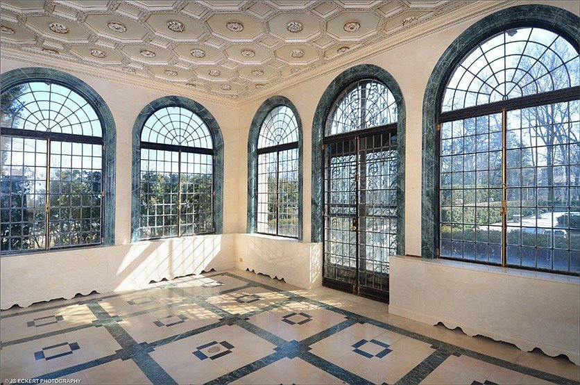 A sun-filled ballroom offers views of the grounds and the lake in the distance. All of the lead glass in the windows was replaced during the restoration. Source: TopTenRealEstateDeals