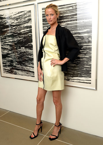 Carolyn Murphy showed off clean lines in a yellow leather dress, a black jacket, and black ankle-strap sandals at an event in NYC.