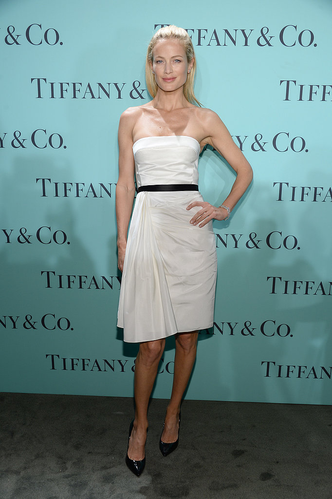 Carolyn Murphy kept things simple and chic in a white strapless dress featuring a black silk waist detail.
