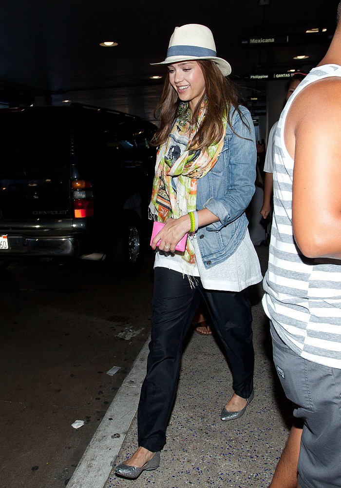 While arriving at LAX, Jessica Alba showcased yet another stellar travel look: a denim jacket, satin jogger pants, a colorful printed scarf, and her Tory Burch fedora.