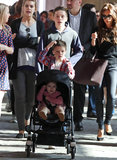 Cruz Beckham pushed Harper Beckham's stroller while Brooklyn Beckham and Victoria Beckham watched on.