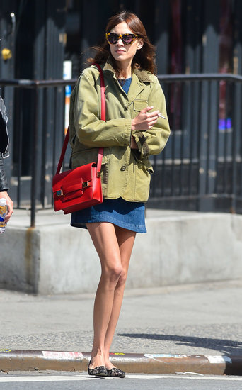 Alexa Chung created the ultimate cool-girl ensemble in NYC: denim dress, olive-green utilitarian jacket, a red structured Delvaux bag, lace loafers, and tortoiseshell sunglasses.