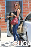 Miranda Kerr wore a black tank and carried a red handbag.