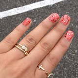 A coral manicure got a funky update with a paint-splatter design and cute rings. Source: Instagram user blackice_87