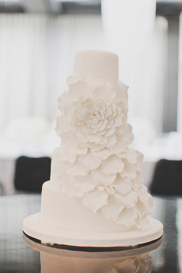 This is one simple but charming cake if we every saw one, with a floral design that takes center stage.  Photo by Kate MacPherson Photographer via Style Me Pretty
