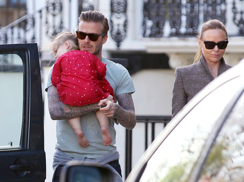 David Beckham walked past Stella McCartney while carrying Harper Beckham,