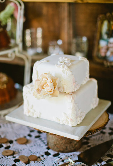 At only two layers high, this pretty white floral-covered cake makes a big impact.  Photo by Sarah Layne Photography via 100 Layer Cake