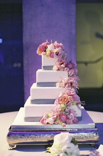 The cascading flowers, purple accents, and four tiers of pretty make this one showstopping cake.  Photo by Caroline Tran Photography via Style Me Pretty