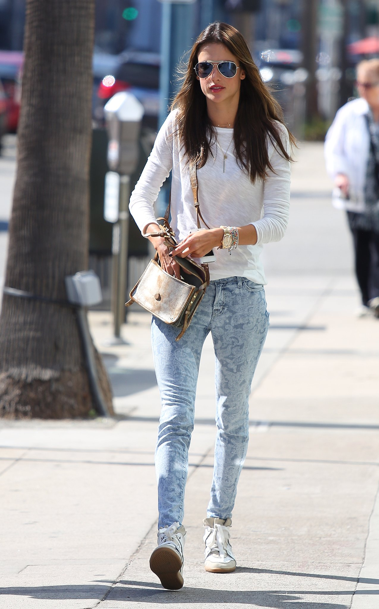 Alessandra Ambrosio's paisley-print jeans were the star of her LA look, while a white long-sleeved tee and white Isabel Maran